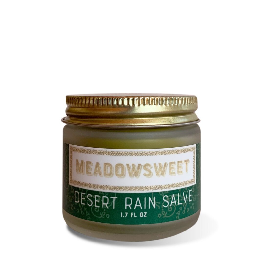 A small glass jar with a gold lid and green and white label containing Desert Rain Salve.