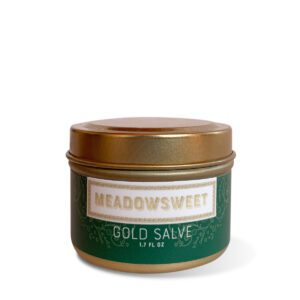 A gold metal jar containing Meadowsweet Gold Salve.