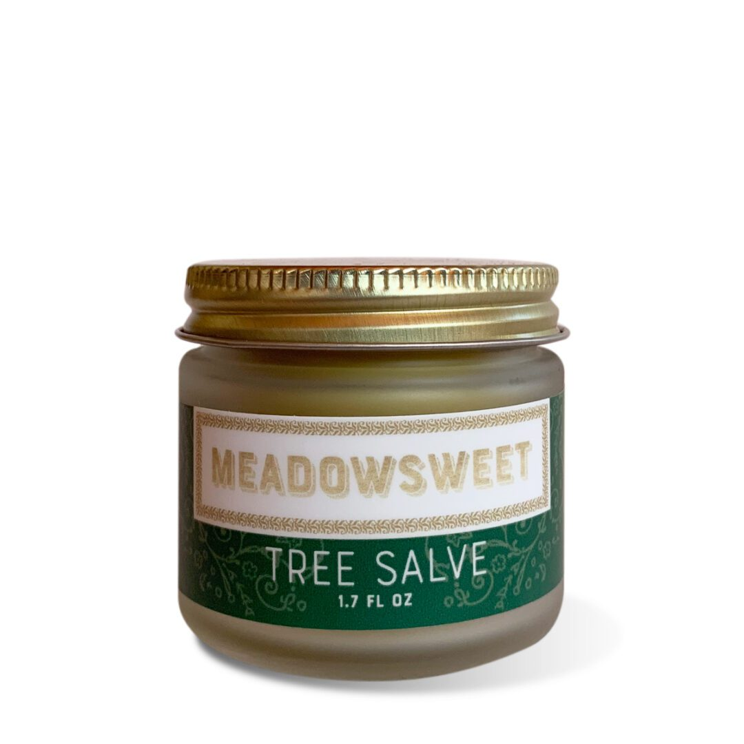 A small frosted glass jar with gold lid and green and white label containing Tree Salve.