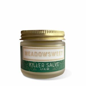 A small frosted glass jar with a gold lid and green and white label containing Killer Salve.