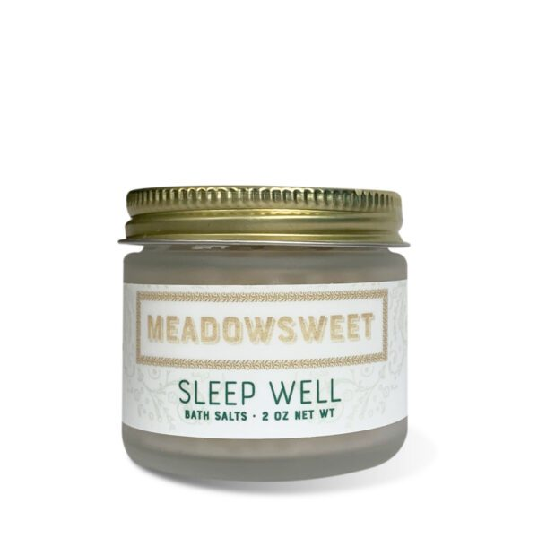 a short frosted jar with a gold lid containing Sleep Well Bath Salts.