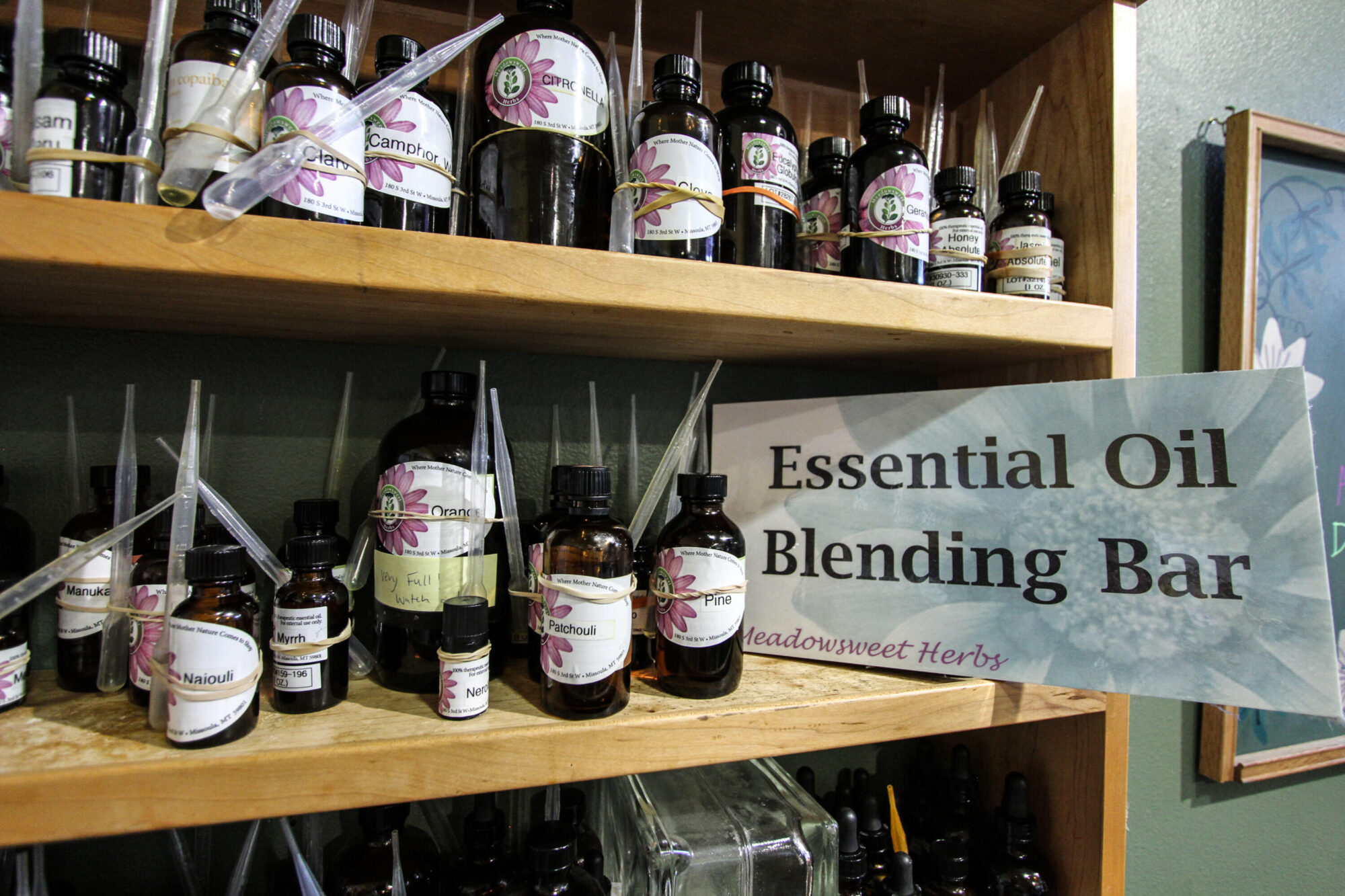 dozens of 1/2 ounce to 4 ounce brown bottles with plastic pipettes contain essential oils on a shelf