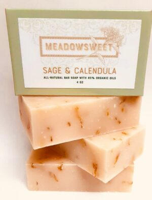 A sage green soap box sits on top of pink soap that contains calendula flower petals