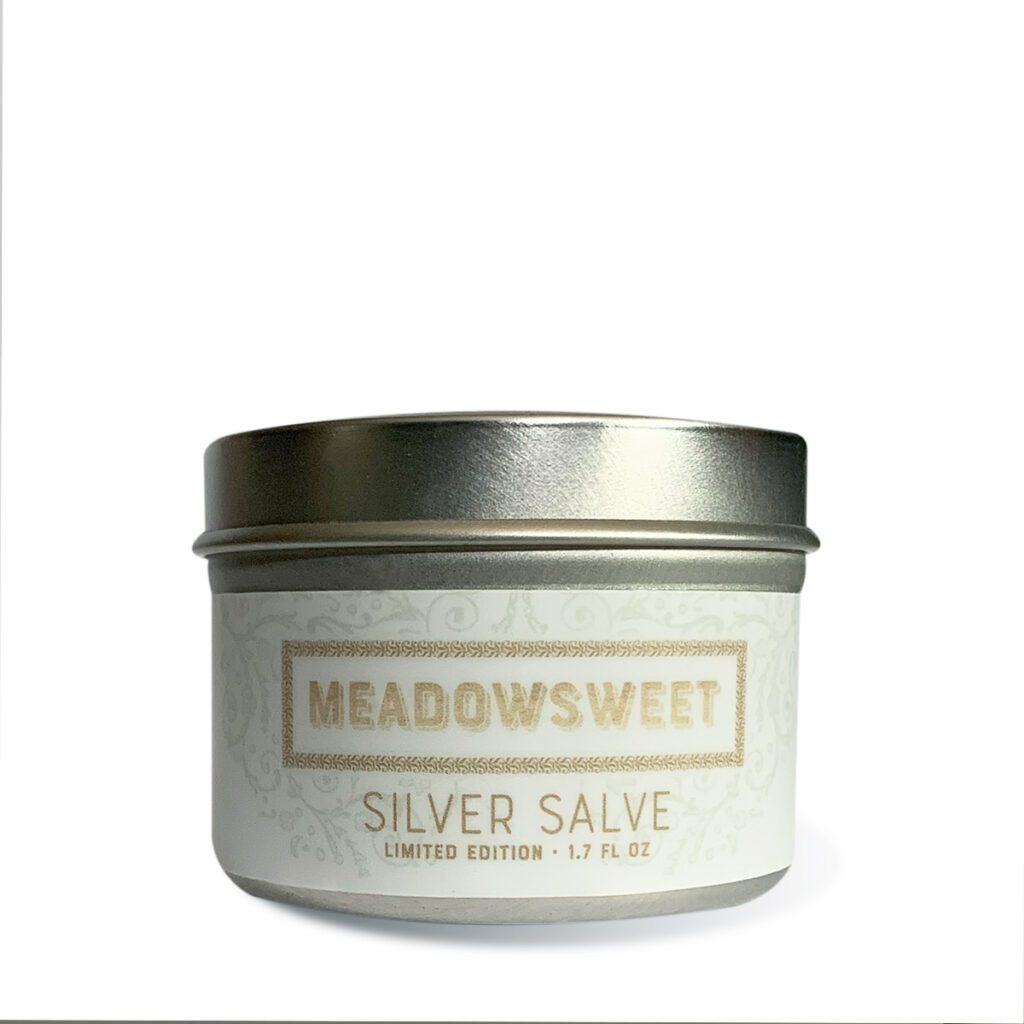 Small silver metal jar with white label containing Silver Salve.